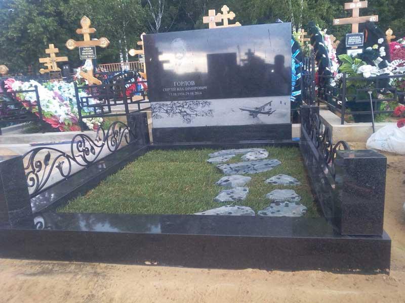 элитный памятник из черного и белого гранита с изображение самолета и кованной оградой