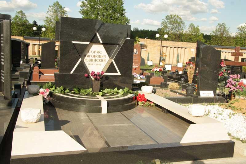 элитный горизонтальный памятник из черного гранита с высеченной белой звездой