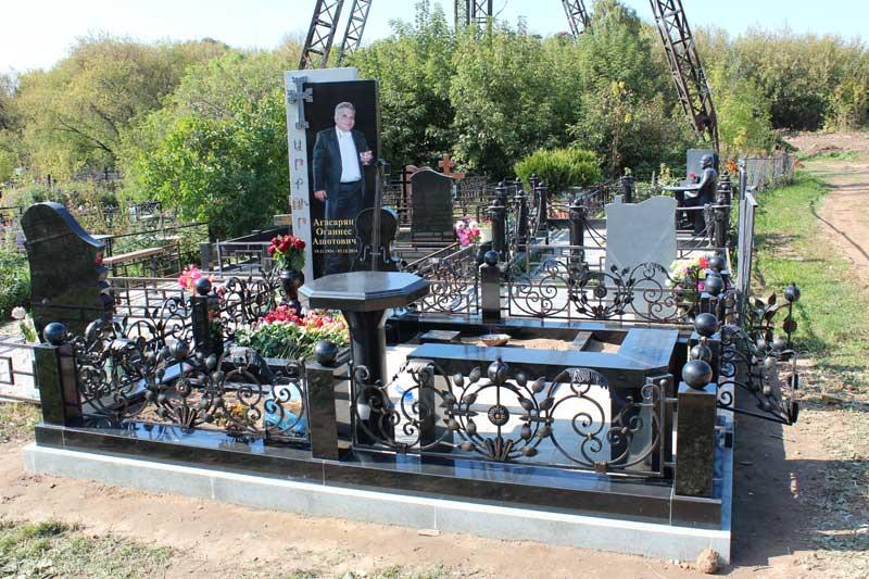 элитный вертикальный мужской памятник из черного гранита с кованной оградой